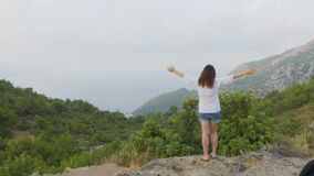 Tourist woman standing on mountain edge with stretching hands. Traveling woman raised hands on green hills landscape. Woman enjoying foggy mountain landscape stock video