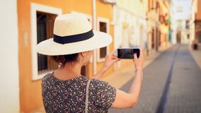 Tourist woman with straw sunhat taking a picture of a narrow street of Denia in Alicante, Spain.