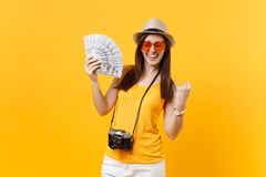 Tourist woman in summer casual clothes, hat holding bundle lots of dollars, cash money isolated on yellow orange royalty free stock photo