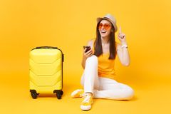 Tourist woman in summer clothes, hat with mobile phone with friend, booking taxi, hotel on yellow orange royalty free stock image