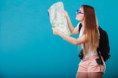 Tourist woman sunglasses read map on blue Royalty Free Stock Photography