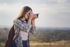 Tourist woman taking photo with her camera in nature stock photography