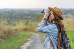 Tourist woman taking photo with her camera in nature stock images