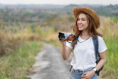 Tourist woman taking photo with her camera in nature royalty free stock photography