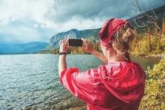 Woman taking photo of lake and mountain. Tourism concept stock photos