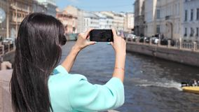 Tourist woman taking photo using smartphone of floating boat river surrounded by historic city. Medium close-up. Travel brunette female shooting video looking stock footage