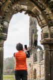 Tourist women taking selfie pictures of the ruins of St Andrews. Tourist woman taking pictures of the ruins of St Andrews Cathedral , Scotland stock photography