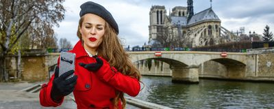 Tourist woman taking selfie with phone on embankment in Paris Stock Photos