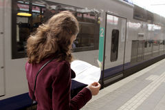 Tourist woman in train station. Tourist woman reading travel guide in train station Royalty Free Stock Photography