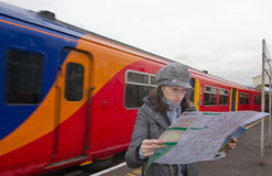 Tourist woman in train station. Tourist woman reading map in train station Stock Photo