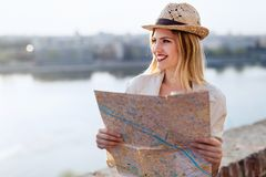 Happy tourist woman on vacation with map visiting city royalty free stock images