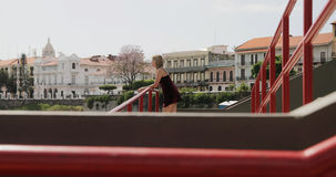 Tourist Woman Visiting Panama City Vacationing In Casco Antiguo. Tourism in Panama City. Young blonde Colombian woman leaning on red rails, visiting Casco Royalty Free Stock Photos