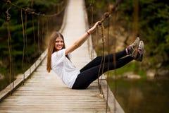 Tourist woman walk by wooden suspension bridge above river stock image
