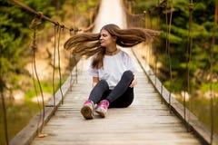 Tourist woman walk by wooden suspension bridge above river stock photo