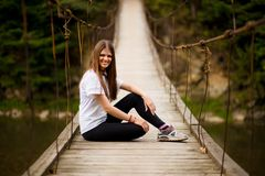Tourist woman walk by wooden suspension bridge above river royalty free stock image