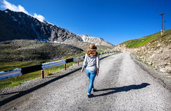 Tourist woman walking at the mountains road Stock Photos