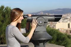 Tourist woman watching city through a telescope Royalty Free Stock Images