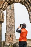 Tourist women taking pictures of the ruins of St Andrews. Tourist woman taking pictures of the ruins of St Andrews Cathedral , Scotland royalty free stock photography