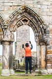Tourist women taking selfie pictures of the ruins of St Andrews. Tourist woman taking pictures of the ruins of St Andrews Cathedral , Scotland royalty free stock photos