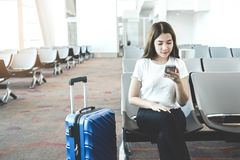 Tourist Women using Phone at international airport waiting for boarding stock photo