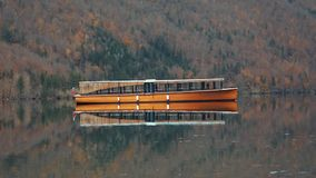 Tourist wooden boat reflection on calm Bohinj lake water. stock footage