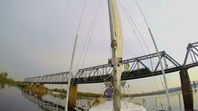 Tourist yacht sailing under river railway bridge, moving train. Stock footage stock video