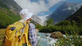 A tourist with a yellow backpack looks at a beautiful glacier at the top of the mountain. Briksdal glacier in Norway. The majestic scenery and beautiful nature royalty free stock image