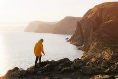 Tourist in yellow jacket looks at cliffs near Sorvagsvatn lake