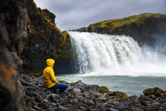 Tourist in a yellow jacket relaxing at the Godafoss waterfall in Iceland