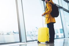 Tourist with yellow suitcase backpack is standing at airport on background large window, traveler man waiting in departure lounge stock image