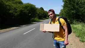 Tourist in a yellow T-shirt catches a car with a backpack and a sign stock footage