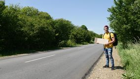 Tourist in a yellow T-shirt catches a car with a backpack and a sign.  Royalty Free Stock Photos