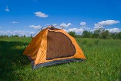 Tourist yellow tent on green lawn. Tourist yellow tent stands on green lawn, in shade of trees Stock Photos