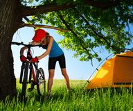 Tourist. Young lady fixing bicycle problems on a meadow with green grass Royalty Free Stock Photos