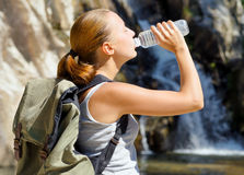 Young woman drinks water by waterfall Royalty Free Stock Images