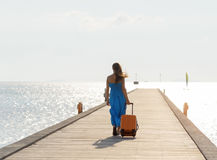 Young woman walking on wooden pier.  Stock Photos
