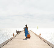 Young woman walking on wooden pier Stock Photo