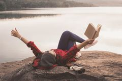 Touriste asiatique de détente de moment lisant un livre sur la roche images libres de droits