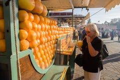 Touriste au chariot de jus d'orange à l'EL Fna de Djamaa d'endroit photo stock