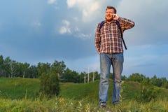 Touriste avec un sac à dos parlant au téléphone Images libres de droits