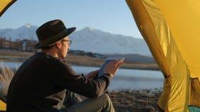 Touriste beau de jeune homme employant le téléphone portable et le mini haut-parleur portatif dans la tente touristique 20s 4k clips vidéos