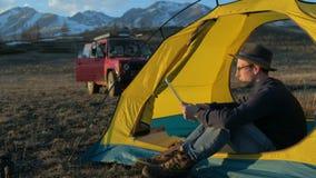 Touriste beau de jeune homme employant le téléphone portable et le mini haut-parleur portatif dans la tente touristique 20s 4k banque de vidéos
