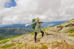 Touriste blonde de fille avec un sac à dos se tenant dans les montagnes de photo stock