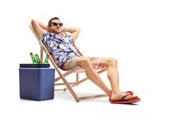 Touriste détendant dans une chaise de plate-forme à côté d'une boîte de refroidissement photographie stock libre de droits