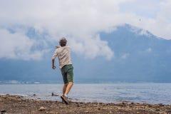 Touriste d'homme au lac Bratan et aux montagnes couvertes du Cl photo libre de droits