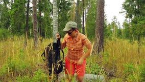Touriste de femme avec un sac à dos dans les bois se reposant sur un arbre tombé clips vidéos