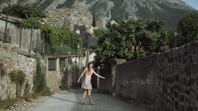 Touriste de femme avec une marche d'appareil-photo Belle vue des maisons blanchies Le jeune photographe féminin porte le chapeau  banque de vidéos