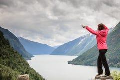 Touriste de femme dans les fjords norvégiens de montagnes photo stock