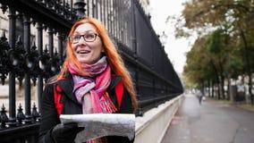 Touriste de femme de Yong avec les cheveux rouges et les verres regardant la carte à Vienne près du Burg de Neue, Autriche photos libres de droits