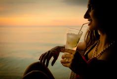 Touriste de femme en cocktail potable de vacances d'été au coucher du soleil Photographie stock